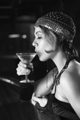 retro female sitting at bar drinking martini.