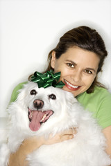 Woman holding white dog.