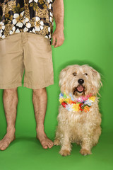 Man standing with dog wearing lei.