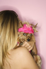 Woman holding Yorkshire Terrier dog.