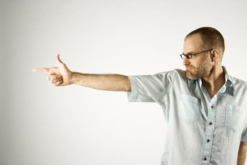 Caucasian man holding hand like gun.