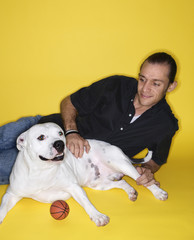 Young adult male Caucasian lying with white dog.
