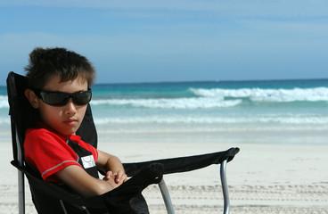 boy on beach chair at beach