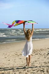 Girl holding kite on beach.