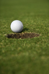 Golf ball close to edge of cup.