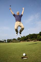 Man jumping for joy over good golf shot.