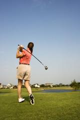 Woman swinging golf club.