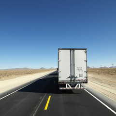 Truck traveling down highway towards horizon.