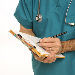 doctor in scrubs making notes on a patient's chart.