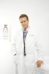 doctor with eye chart in background.