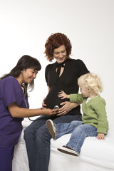 nurse holding stethoscope on pregnant woman's belly.