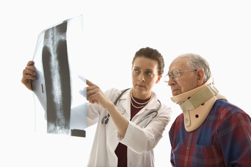 doctor ponting at x-ray with elderly man in neck brace looking o