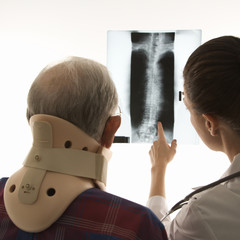 over the shoulders view of doctor pointing at an x-ray as elderl