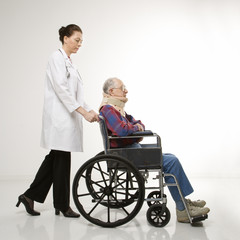 doctor pushing elderly man with neck brace in wheelchair.