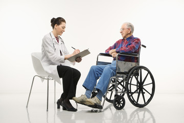 doctor taking notes with an elderly man in wheelchair to her sid
