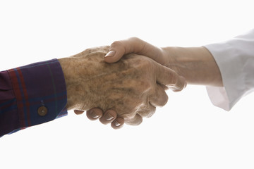 close-up of elderly man shaking hands with female hand.