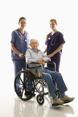 two women wearing scrubs with elderly man in wheelchair.