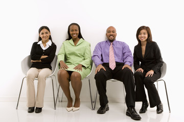 multi-ethnic business group sitting and smiling.