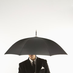 businessman with face covered by umbrella.