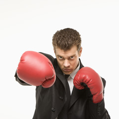 man in suit wearing boxing gloves.