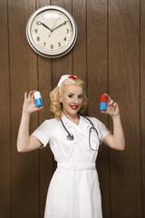 female nurse in retro uniform holding giant pills.