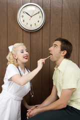 female nurse examinating man's mouth.