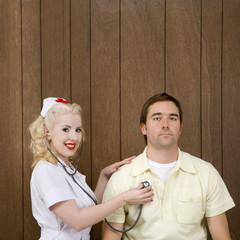 female nurse checking man's heartbeat.