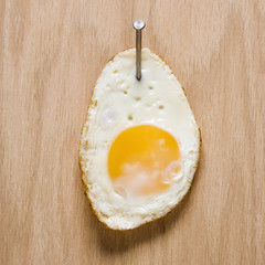 fried egg nailed to wood.