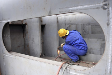 Welder with protective mask welding metal at Double bottom Cargo Ship