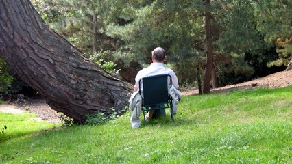 man/ elderly sitting relaxing on a chair