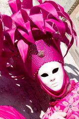 a venetian in a pink costume and white mask