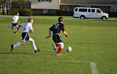 boys playing soccer on grass