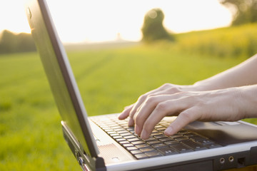 typing on a laptop outside
