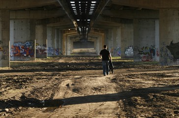 a person walking under an old bridge