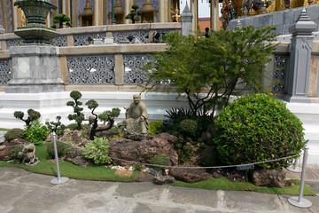 budha skulptur zwischen bonsai