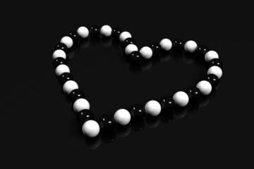 collier coeur perles noir et blanc sur fond noir
