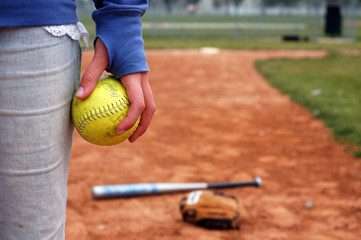 a girl and her softball, glove, and bat