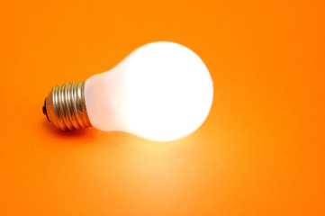 lit bulb on orange background