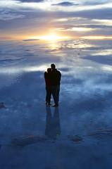 couple watching sunset over wet salt flats