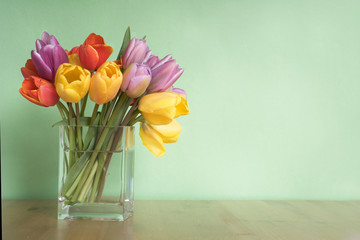 vase of tulips on table - green background