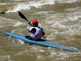 Competitive whitewater kayaker heading into a rapids