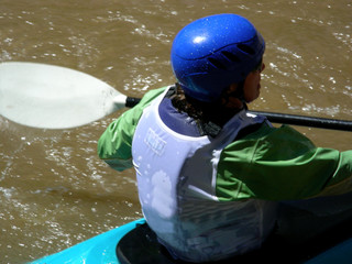Female white water kayaker heading down the river