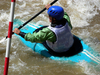 Competitive female kayaker navigating through a gate