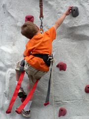 Young climber reaching for the next hand hold
