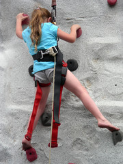 Young girl scaling a climbing wall barefoot