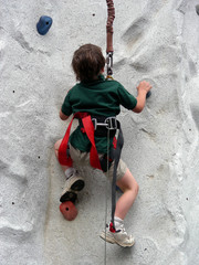 Little boy climbing a rock wall like a little bug