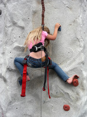 Young girl climbing a rock wall barefoot