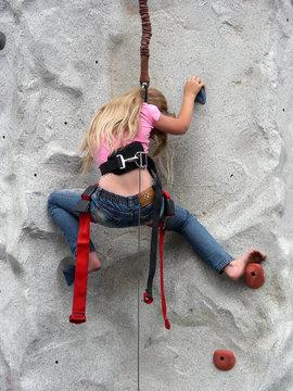 Young girl climbing a rock wall barefoot