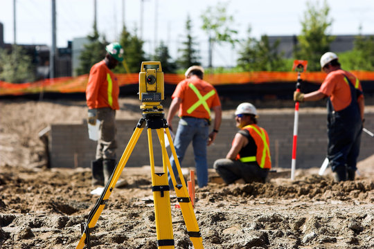 Level on a tripod with construction workers in the background.