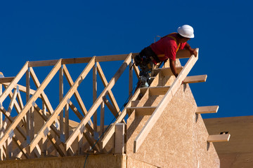 Carpenter building a roof of a house at a construction site.
